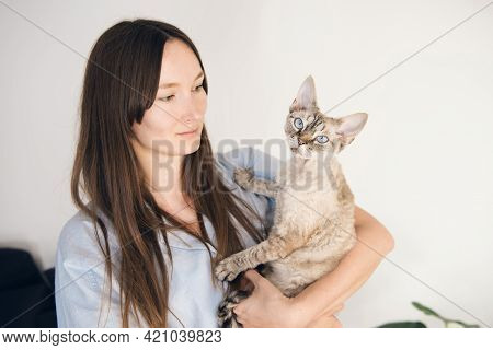 Young Woman Posing With Devon Rex Feline At Home Interior. Cat Is Sitting In Owners Arms And Gives B