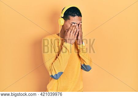 Young african american guy listening to music using headphones rubbing eyes for fatigue and headache, sleepy and tired expression. vision problem
