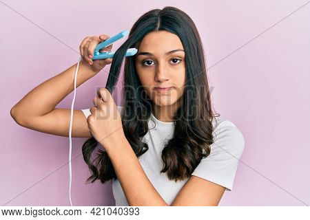 Young hispanic woman holding hair straightener skeptic and nervous, frowning upset because of problem. negative person.