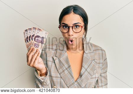 Young brunette woman holding 500 mexican pesos banknotes scared and amazed with open mouth for surprise, disbelief face