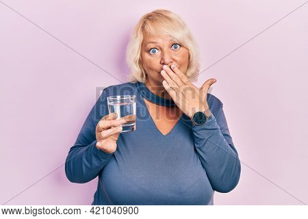 Middle age blonde woman drinking glass of water covering mouth with hand, shocked and afraid for mistake. surprised expression