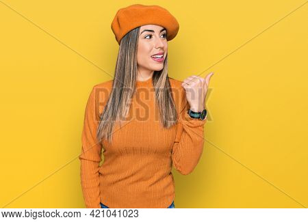 Young hispanic woman wearing french look with beret smiling with happy face looking and pointing to the side with thumb up.