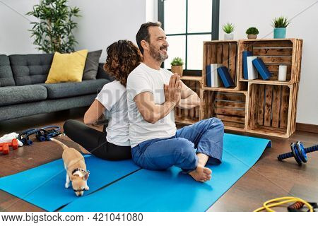 Middle age hispanic couple smiling happy doing yoga at home.