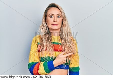 Beautiful young blonde woman wearing colored sweater pointing aside worried and nervous with forefinger, concerned and surprised expression
