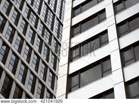 Close Up Detail Of Tall High Rose Modern Apartment Buildings With White Cladding And Dark Windows