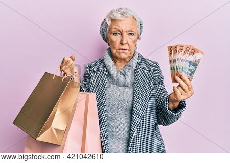 Senior grey-haired woman holding shopping bags and australia dollars depressed and worry for distress, crying angry and afraid. sad expression.