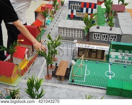 A Boy In Black Clothes Reaches Out To A Table With A Paper Model - A Model Of A City Or District. Sc