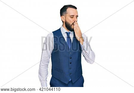 Young man with beard wearing business vest bored yawning tired covering mouth with hand. restless and sleepiness.