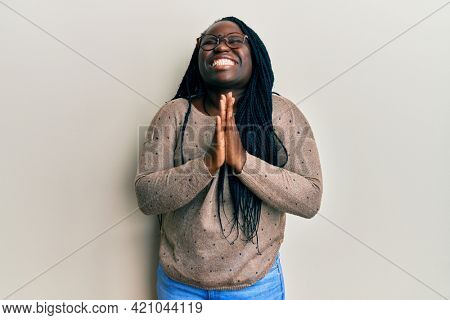 Young black woman with braids wearing casual clothes and glasses begging and praying with hands together with hope expression on face very emotional and worried. begging.