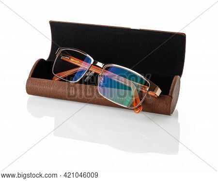 Eyeglasses With Golden Rim In An Open Brown Case Isolated On A White Background. Glasses For Vision