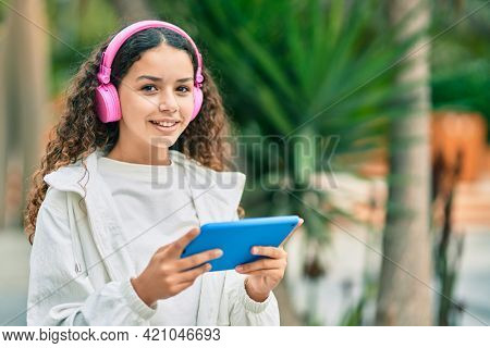 Hispanic child girl smiling happy using headphones and touchpad at the city.