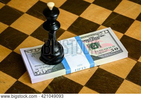 Chess King And Dollar Bills Stack On Chessboard, Us Paper Currency And Game. Concept Of Money Strate