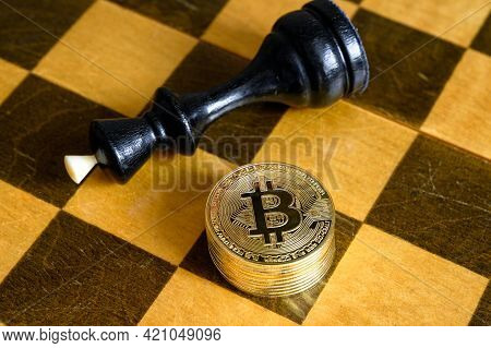 Chess King And Bitcoin On Wooden Chessboard, Gold Bit Coins Stack And Game Over. Concept Of Financia