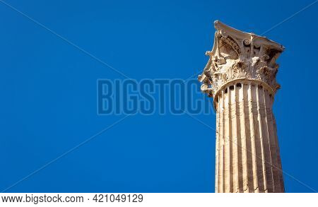 Ancient Corinthian Column On Blue Sky Background, Athens, Greece. Detail Of Old Temple Of Olympian Z