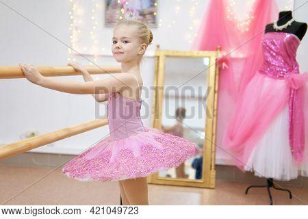 Little ballerina training. Children dance сlassical ballet in studio.