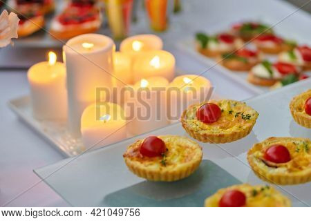 Romantic catering table, set service at restaurant before party. Candle and snack. Food design.