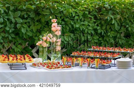 Romantic catering table, set service at restaurant before party. Food design.