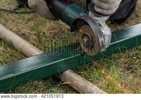 A Strong  Man Welder  Grinder Metal An Angle Grinder  On The Grass In The Village