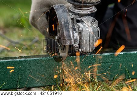 Close-up On The Sides Fly Bright Sparks From The Angle Grinder Machine. A Young Male Welder In A  Wo