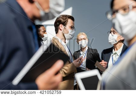 Multiethnic Business People In Medical Masks Talking During Break In Seminar, Blurred Foreground.