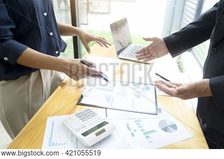 Businessmen And Teamwork  Are Standing Look To Graph Chart And Discussing Documents On The Table To