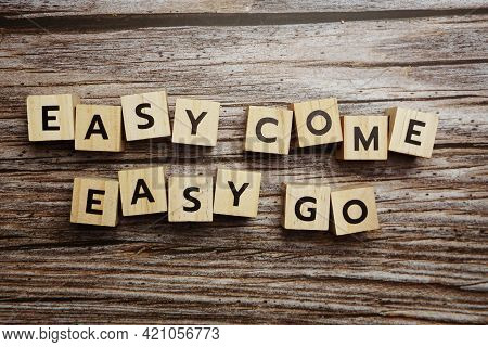Easy Come  Easy Go Alphabet Letters On Wooden Background;