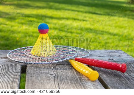 Badminton Game Rackets And Shuttlecock On Wooden Table With Green Grass In The Park On A Sunny Summe