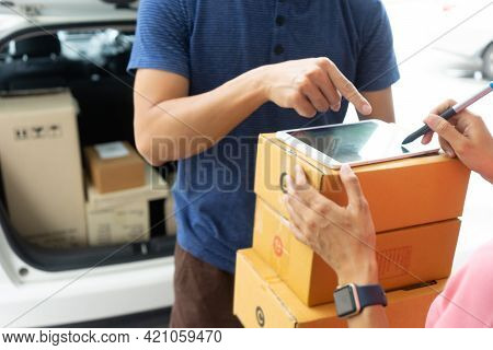 The Courier Stood Holding The Box With A Smile Delivering The Product Box To The Customer Who Was Si