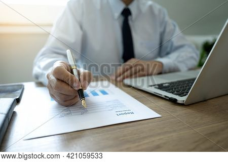 A Businessman Holding A Pen To Write Documents On The Desk