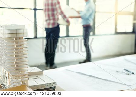 Focus On The Building Model Houses Architect Or Engineer Standing Near The Window Talking About  Bus
