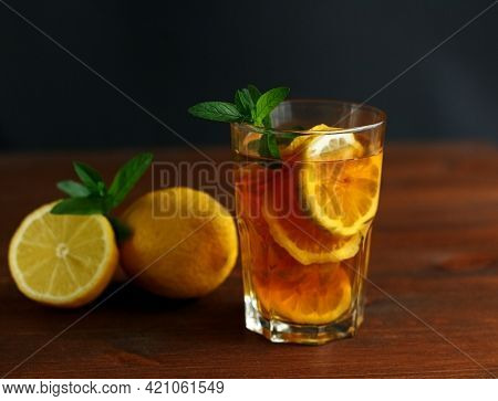 Glass Of Iced Tea With Lemon Slices And Mint On A Wood Background.