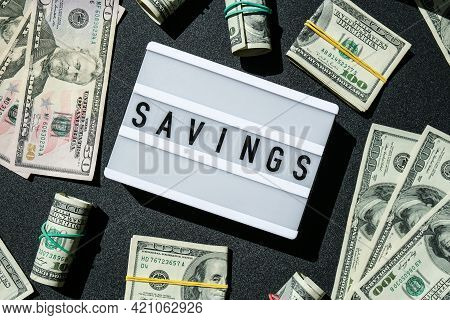 Lightbox Board With Word Savings In Black Letters Around Us Dollar Banknotes. Money, Business, Finan
