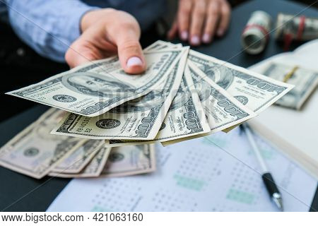 Business Woman Displaying A Spread Of Cash Us Dollars. Close-up. Income And Business Concept. Venali