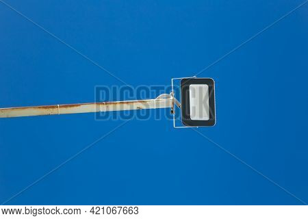 The Floodlight On A Long Metal Leg Is Directed Downward. Close-up Against The Clear Blue Sky. There