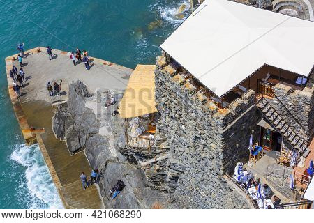 Vernazza, Cinque Terre - Italy, May 12, 2019: View On Tourists On Stone Pier, Outdoor Restaurant Ove