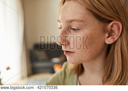 Freckled Girl Looking Attentively At The Canvas While Sitting In Front Of The Easel