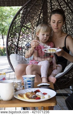 Mom And Daughter Have Breakfast On The Open Veranda