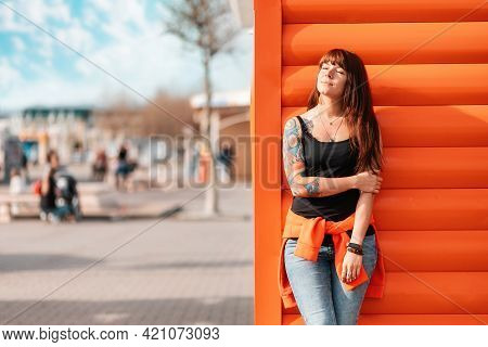 A Young Beautiful Woman With Closed Eyes With Tattoos On Her Arm, Posing Near A Wooden Wall. Outdoor