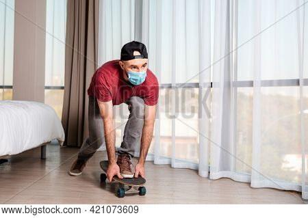 A Young Man In A Medical Mask, Riding A Longboard. Home Interior. Indoors. Concept Of Quarantine And