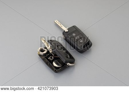 Broken Or Damaged Car Key Fob And New Remote Vehicle Key On Grey Background. Repair Of Broken Or Dam
