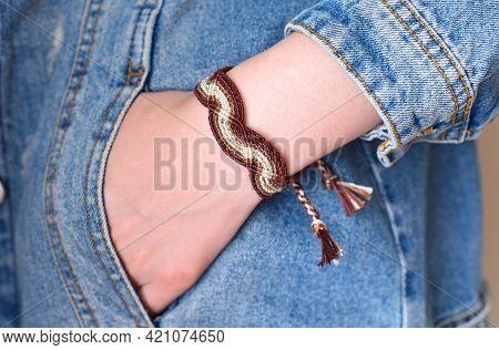 Diy Woven Tied Friendship Bracelet On A Wrist. Hand In Pocket