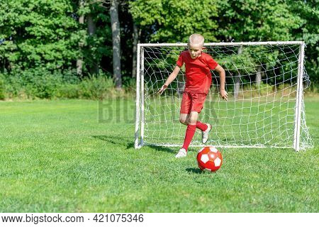 A Young Soccer Player-goalkeeper In A Red Uniform Catches The Ball, Defending The Goal. Children\'s