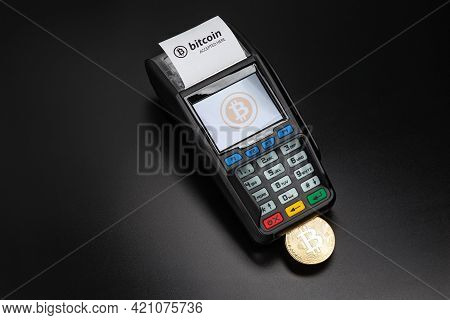 Payment Terminal Ready To Accept Bitcoins For Payment On The Black Background. Bitcoin Gold Coin Sti