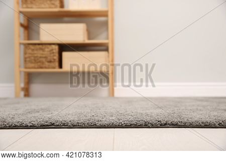 Room With Shelving Rack And Light Wall, Focus On Soft Grey Carpet. Space For Text