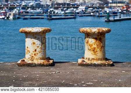 Two Pillar Bollards For Mooring Boats With The Harbour In The Background. Each White Painted Steel M