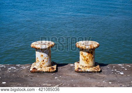 Two Pillar Bollards For Mooring Boats On A Harbour Wall. Each White Painted Steel Mooring Bollard Is