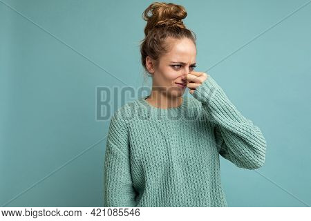 Portrait Of Young Dissatisfied Beautiful Blonde Woman With Sincere Emotions Wearing Casual Blue Pull