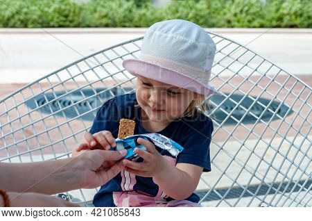 Mom Feeds Baby In The Park. A Healthy Snack. A Girl Sits On A Street Chair And Holds A Snack. She Is