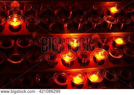 Candles Burning In The Glass Cups . Church Interior With Candlesticks . Fire In The Glass