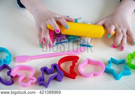 Girl Toddler Forming And Shaping Plasticine Or Play Clay By Hands And With Yellow Rolling Pin. Play